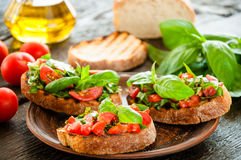 Italian bruschetta with chopped vegetables, herbs and oil on gr Stock Image