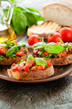 Italian bruschetta with chopped vegetables, herbs and oil on gr Royalty Free Stock Photos