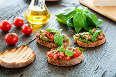 Italian bruschetta with chopped vegetables, herbs and oil on gr Stock Photo