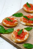 Italian bruschetta. Fresh bruschetta with tomato and basil on cutting board Stock Photo
