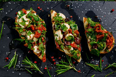 Italian bruschetta with roasted tomatoes, mozzarella cheese and herbs Royalty Free Stock Photography