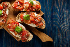 Italian bruschetta with roasted tomatoes, mozzarella cheese and. Herbs on a cutting board Stock Photos