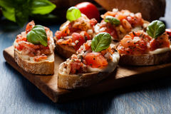 Italian bruschetta with roasted tomatoes, mozzarella cheese and royalty free stock images