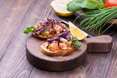 Italian bruschetta with roasted vegetables, salmon, onion and herbs on a cutting board. Old wooden table background Stock Images