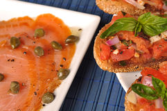 Italian bruschetta and salmon. Italian bruschetta, toast with tomato and spices and salmon with capers Stock Photo