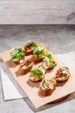 Italian bruschetta with salmon, tomatoes, cheese and basil pesto on a grey concrete or stone background. Italian bruschetta with tomatoes, feta and basil pesto Stock Photo