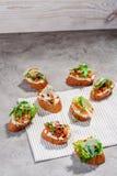 Italian bruschetta with salmon, tomatoes, cheese and basil pesto on a grey concrete or stone background. Italian bruschetta with tomatoes, feta and basil pesto Stock Images