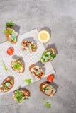 Italian bruschetta with salmon, tomatoes, cheese and basil pesto on a grey concrete or stone background. Italian bruschetta with tomatoes, feta and basil pesto Royalty Free Stock Photos