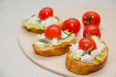 Italian bruschetta with soft cheese, tomatoes, rosemary and fresh salad on the plate. Space for text Stock Photography