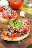 Italian bruschetta with tomato, olives, basil and cheese closeup Royalty Free Stock Photo