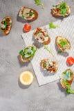 Italian bruschetta with salmon, tomatoes, cheese and basil pesto on a grey concrete or stone background. Italian bruschetta with tomatoes, feta and basil pesto Royalty Free Stock Photo