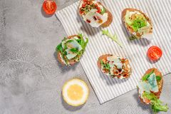 Italian bruschetta with salmon, tomatoes, cheese and basil pesto on a grey concrete or stone background. stock photography