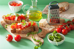Italian bruschetta with tomatoes parmesan arugula.  royalty free stock photography