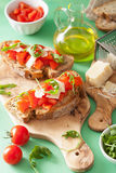 Italian bruschetta with tomatoes parmesan arugula Stock Photo