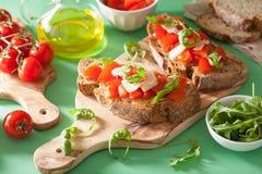 Italian bruschetta with tomatoes parmesan arugula Stock Images