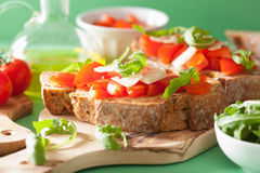 Italian bruschetta with tomatoes parmesan arugula Stock Images
