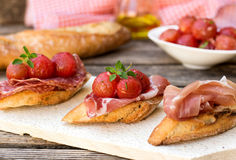 Italian bruschettas with ham prosciutto, coppa, salami, cherry t Royalty Free Stock Photography