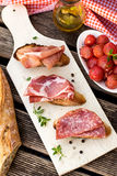 Italian bruschettas with ham prosciutto, coppa and salami Royalty Free Stock Images