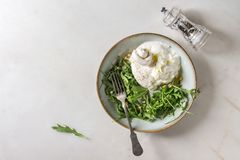 Italian burrata cheese. Sliced Italian burrata cheese, black pepper mill, fresh arugula salad, pine nuts and olive oil in white ceramic plate over white marble stock image