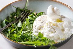 Italian burrata cheese. Sliced Italian burrata cheese, fresh arugula salad, pine nuts and olive oil in white ceramic plate on cloth over white marble table stock photo