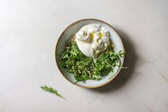 Italian burrata cheese. Sliced Italian burrata cheese, fresh arugula salad, pine nuts and olive oil in white ceramic plate over white marble background. Flat lay royalty free stock photos