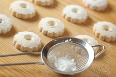 Italian canestrelli cookies and a strainer with powdered sugar. Italian canestrelli biscuits arranged on a raw wooden table with a strainer full of powdered royalty free stock images