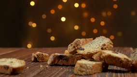 Italian cantucci with almond and cranberries. Falls on a wooden surface against the background of Christmas light strings stock video footage