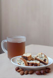 Italian cantuccini cookies. Still life of traditional home made crumbly Italian cantucci cookies with hazelnut and almond on white plate together with a cup of Royalty Free Stock Photography