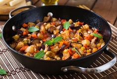 Italian Caponata with frying pan. Italian Caponata with frying pan on a wooden background Stock Image
