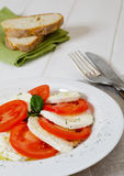 Italian caprese salad. With basil, fresh mozzarella, tomatoes, olive oil and bread Stock Photos
