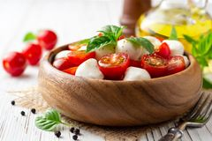 Italian caprese salad with cherry tomatoes, mozzarella cheese and basil on white wooden background. Selective focus stock photo