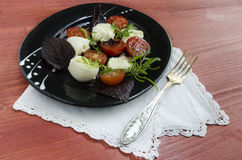 Italian caprese salad with fresh basil leaves, tomato and  mozzarella  on red wooden table. Stock Image