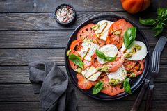 Italian caprese salad. With sliced tomatoes, mozzarella cheese, basil, olive oil. Served on black plate over dark wood background. Top view. Rustic style stock photography