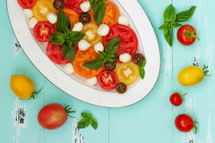 Italian caprese salad with mozarella cheese, tomatoes and basil on vintage wooden background. Top view, free text copy space Stock Photos