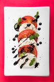 Italian Caprese salad with Mozzarella Tomato Oregano Black Pepper and Balsamic Vinegar on White Plate on Red Background Royalty Free Stock Photography