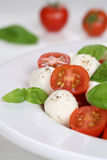 Italian Caprese salad with tomatoes and mozzarella cheese on a p Stock Photos