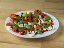 Italian caprese salad on white plate  tomatoes basil an mozzarel. La on wooden desk Stock Images