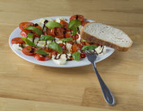 Italian caprese salad on white plate  tomatoes basil an mozzarel. La on wooden desk with fork and bread Stock Photography