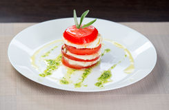 Italian Caprese. Tomato and mozzarella lies on a plate Stock Photos