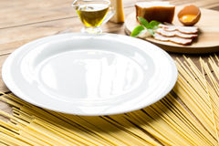 Italian carbonara ingredients with empty plate on wooden background Royalty Free Stock Images