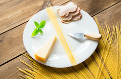 Italian carbonara ingredients with empty plate on wooden background Stock Image