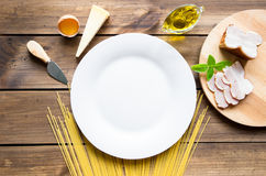 Italian carbonara ingredients with empty plate on wooden background Royalty Free Stock Photos