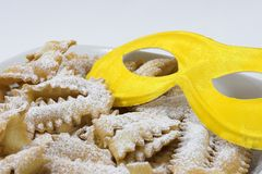 Italian carnival sweet food. Close-up of italian carnival sweet food with yellow mask Royalty Free Stock Photo