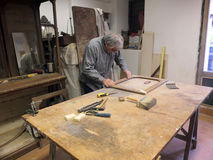 Italian carpenter. Carpenter while working in his workshop in Rome Stock Image