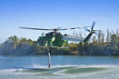 Italian CFS 103 fire fighting helicopter flying over a lake to collects water through a suction tube to extinguish a fire.  royalty free stock images