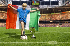 Italian Champions. Young child, proudly holding a large Italian flag stands like a champion in the center of a large soccer stadium Royalty Free Stock Image
