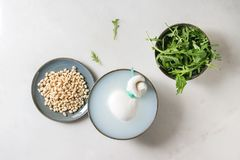 Italian cheese burrata. Bowl with whole tied Italian cheese burrata in brine, arugula salad and pine nuts over white marble background. Flat lay, space royalty free stock photo