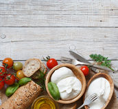 Italian cheese burrata with bread, vegetables and herbs Stock Photos