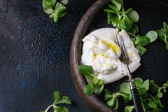 Italian cheese burrata. Sliced Italian cheese burrata with vintage fork, fresh corn salad and olive oil in clay tray over dark textural background. Overhead view royalty free stock photo