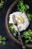 Italian cheese burrata. Sliced Italian cheese burrata with vintage fork, fresh corn salad and olive oil in clay tray over dark textural background. Overhead view stock image